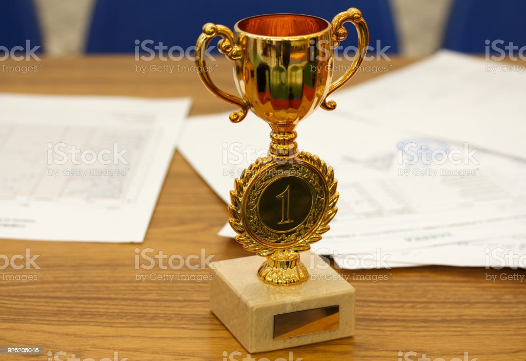 Congratulatory letter. Golden cup award trophy and document with a seal on wooden table stock photo