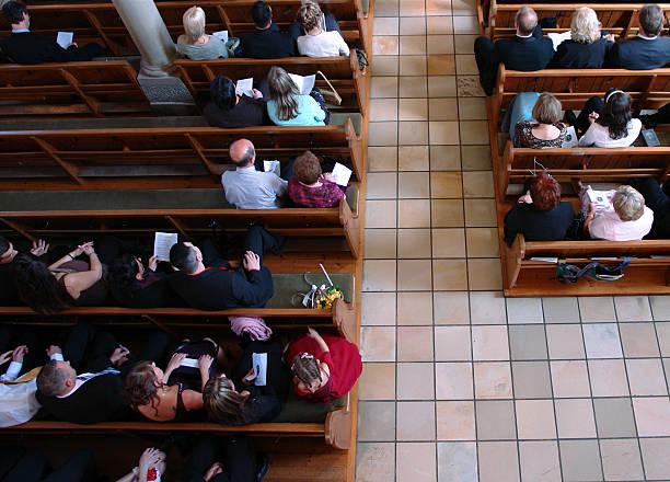 congregation at church praying - kilise stok fotoğraflar ve resimler