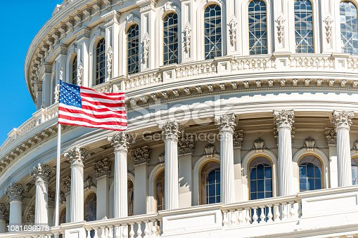 istock US Congress dome closeup with American flag waving in Washington DC, USA on Capital capitol hill, blue sky, columns, pillars, nobody 1081696978