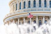US Congress dome closeup with background of water fountain splashing, American flag waving in Washington DC, USA closeup on Capital capitol hill, columns, pillars, nobody