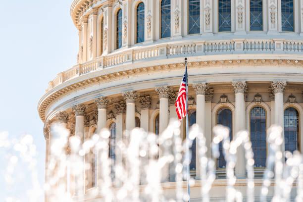 Abóbada do Congresso dos E.U. com o primeiro plano da fonte de água que espirra e bandeira americana que acena em Washington DC - foto de acervo