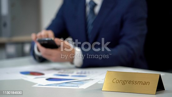 1130184417 istock photo Congressman with smartphone working on diagram reports, preparing for election 1130184530