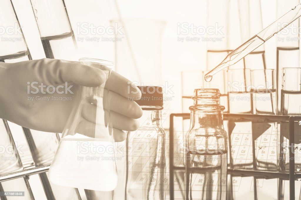 Conical flask in scientist hand with lab glassware background, Laboratory research concept,Ancient image process syle stock photo