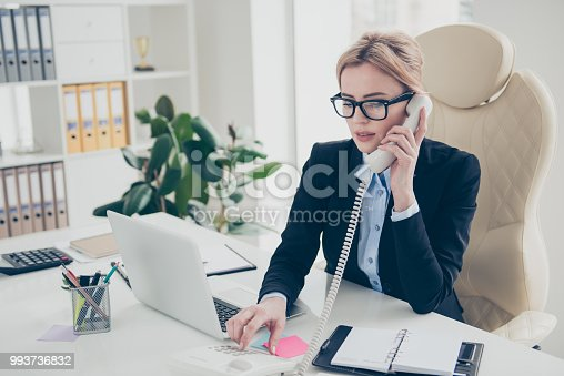 istock Connect line concept. Portrait of stylish smart lawyer in eyewear speaking by telephone using handset dialing number calling partners sitting in modern work place 993736832