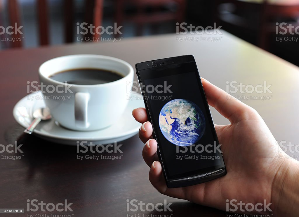 """Connect the world Social networking/mobility  consept. Woman holding mobil phone displaying """"world"""" in a coffee shop. Earth image from NASA Earth observotery. http://visibleearth.nasa.gov/view_detail.php?id=2429 Accessibility Stock Photo"""