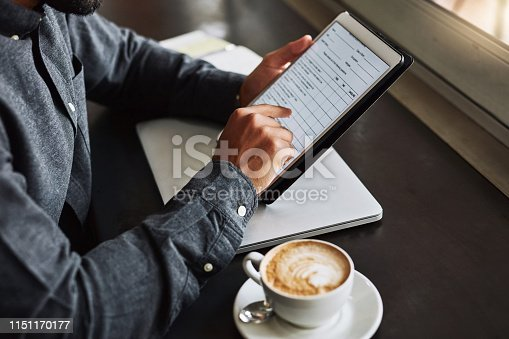 Cropped shot of an unrecognizable man using a digital tablet while sitting in a coffeeshop