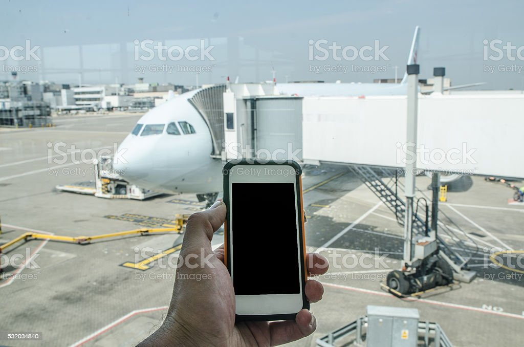 Connected at the airport with cell phone stock photo