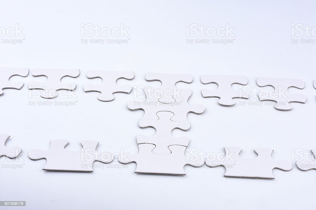 Connected blank puzzle pieces isolated on a white background. stock photo