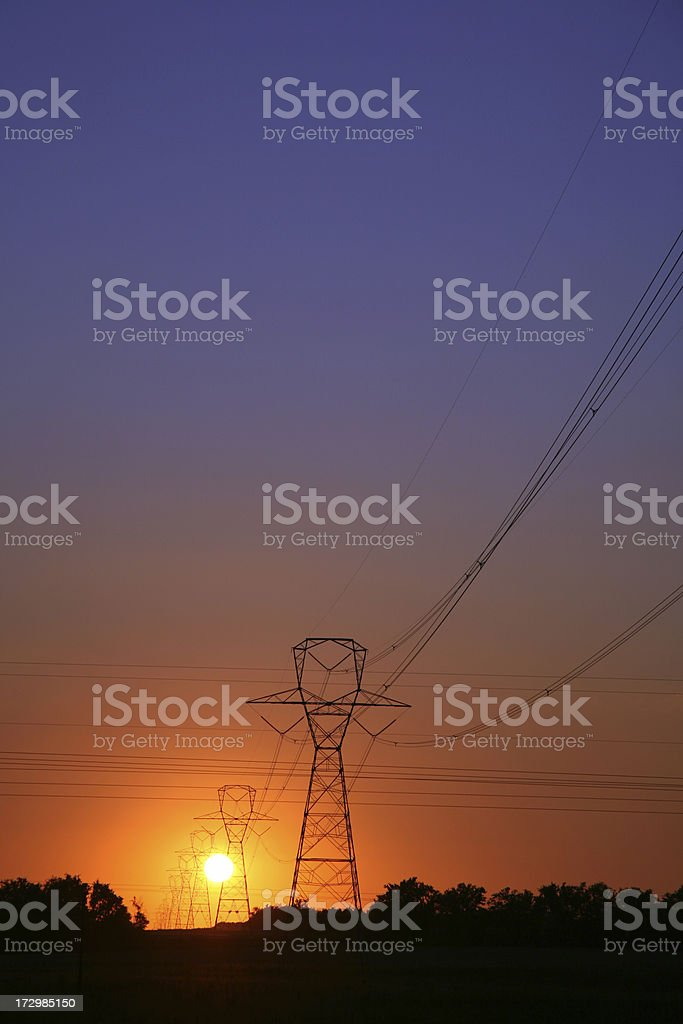 Connected electric energy power lines towers at sunrise stock photo