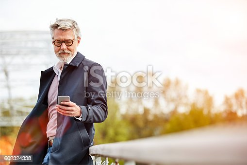 Shot of a mature man using a cellphone while leaning on a railing in the city