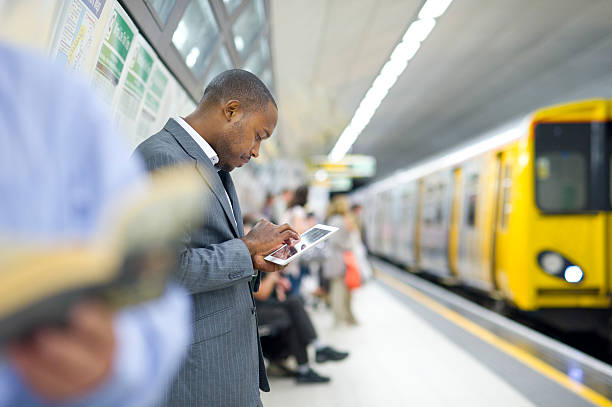 connected in the subway young man checking his emails in the subway subway platform stock pictures, royalty-free photos & images