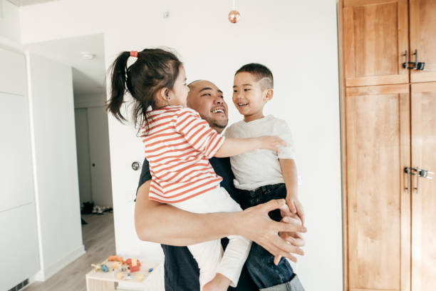 Connected parenting Dad hugging kids southeast asian ethnicity stock pictures, royalty-free photos & images