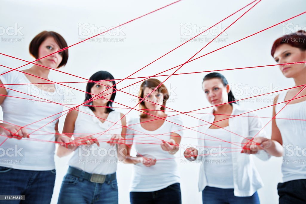 connected to the network Network concept. Group of women holding red rope. 30-34 Years Stock Photo