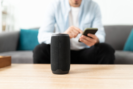 Closeup of a man connecting his smartphone and bluetooth speaker to his smart home system