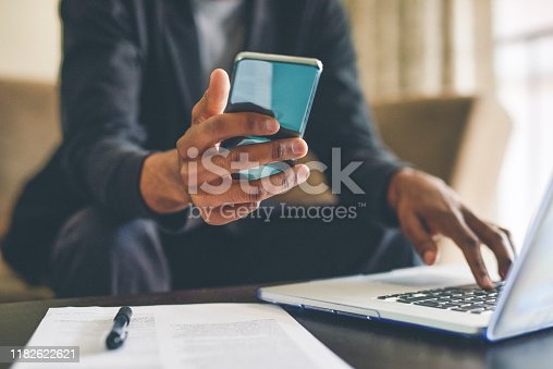 Cropped shot of an unrecognizable man using a smartphone and a laptop while working from home