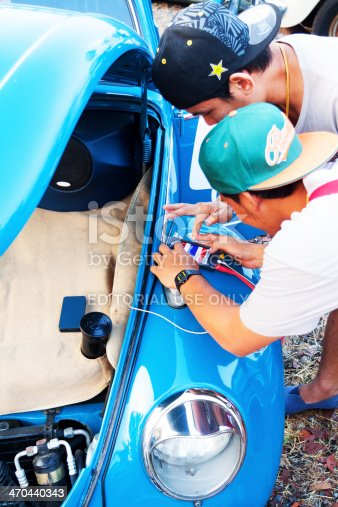 Bangkok, Thailand - February, 15th 2014: Two Thai men are connecting mobile iPhone to soundsystem of old restored VW Beetle. Front bonnet is open and inside is huge speaker with VW design. Men are wearung caps. Old VW is standing on parking space close to Wonder World Extreme Park opposite side to Fashion Island. On parking space is local VW meeting and festival with many private owners of old VW showing their old cars to people or sell cars or replacments.