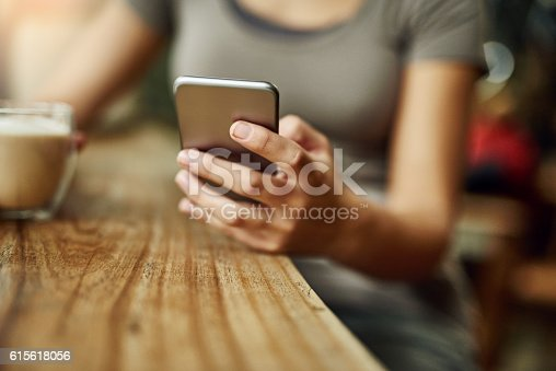 Closeup shot of a young woman using a cellphone and drinking a coffee while sitting in a cafe
