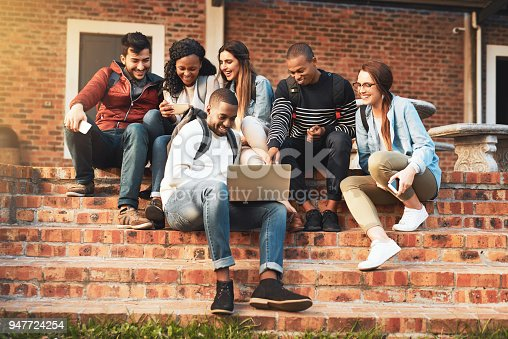 Shot of a group of students using a laptop together on campus