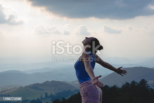 Woman enjoying nature on mountain view in sunset with arms outstretched expressing happiness.