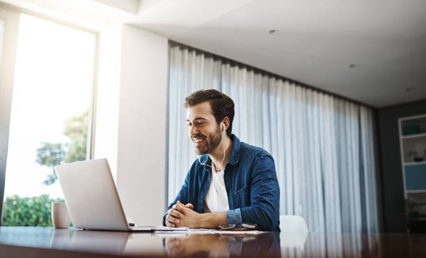 Connecting with the business world anywhere, anytime Shot a handsome young businessman sitting down and using his laptop to take a video call while working from home conference call stock pictures, royalty-free photos & images
