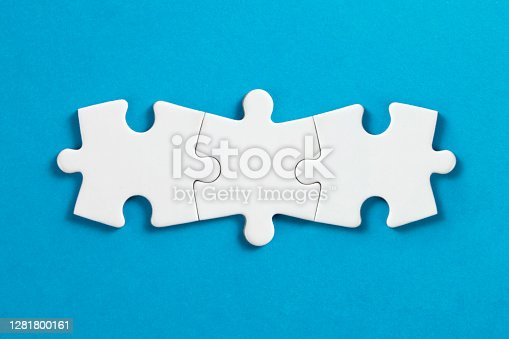 White puzzle pieces comes together on blue background.