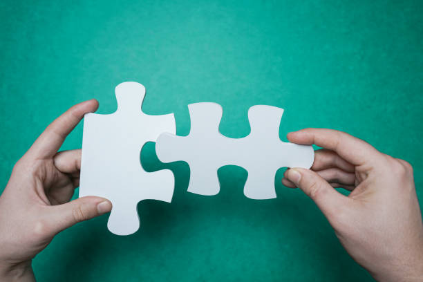 Connection. Hands trying to fit two puzzle pieces together. stock photo