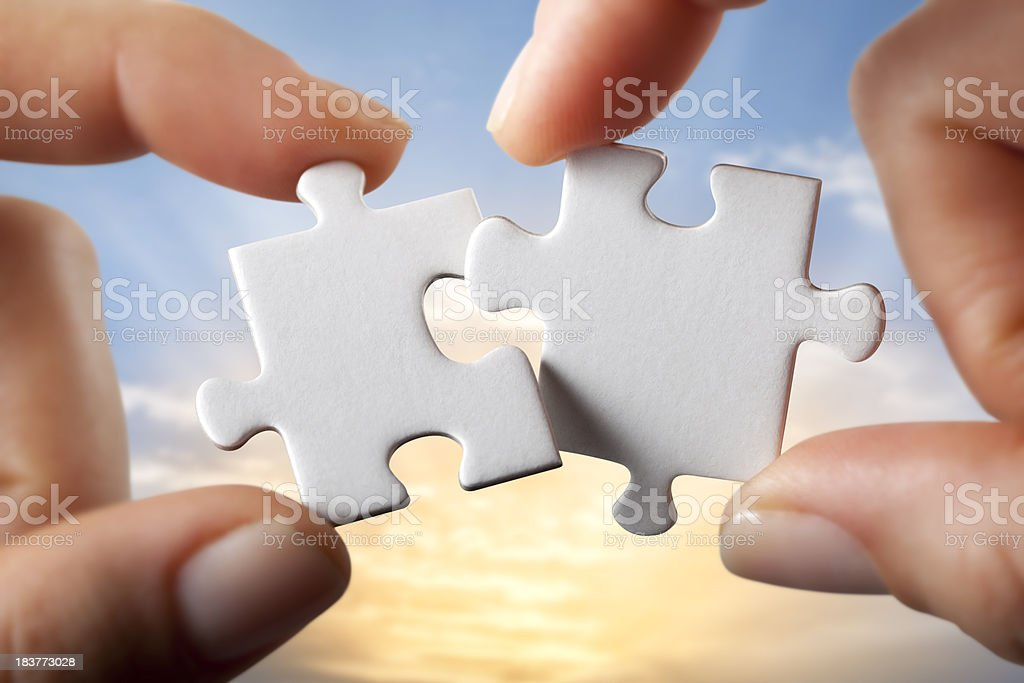 Connection. Hands trying to fit two puzzle pieces together. royalty-free stock photo