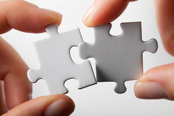 conexão. mãos tentando ajuste duas peças de quebra-cabeça em conjunto. - dois objetos - fotografias e filmes do acervo