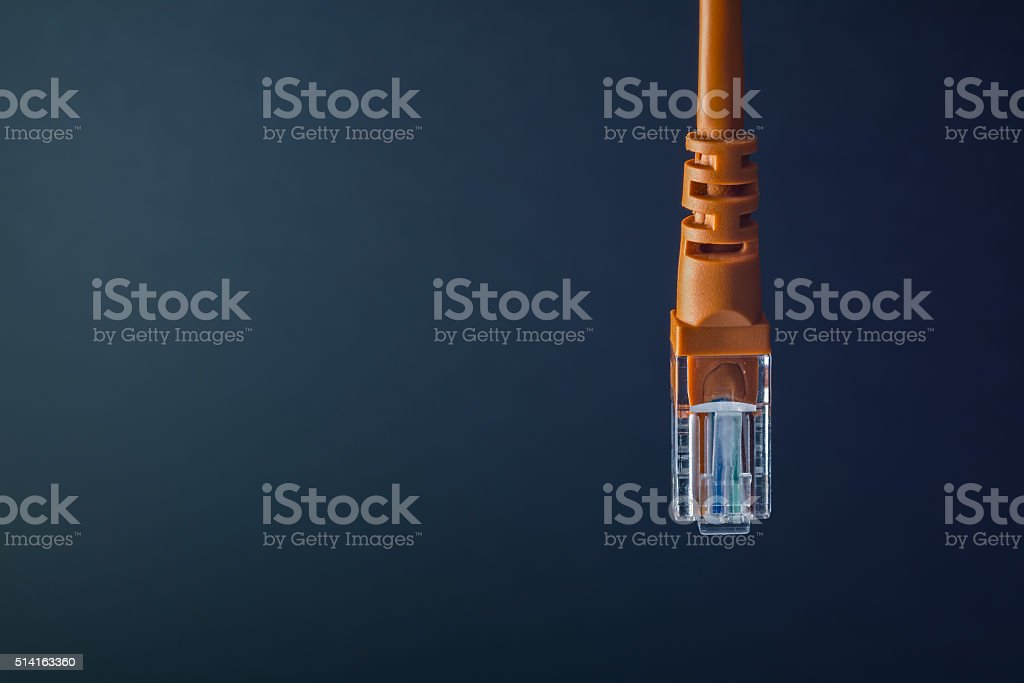 LAN connection orange plastic connector isolated on black background stock photo