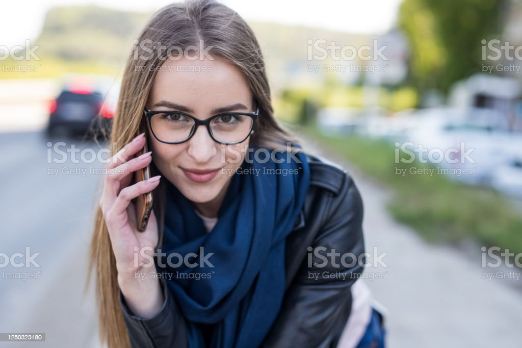 Connection with friends is important Alone young woman with protective mask and cell phone sitting on a staircase and talking with her friends out side Adult Stock Photo