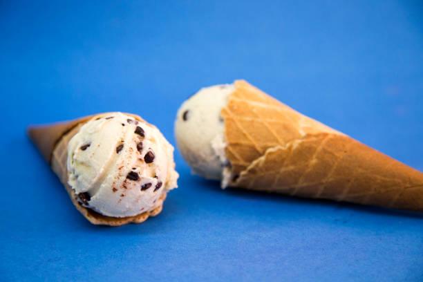 cono de helado Cono de helado, fondo azul cono gelato stock pictures, royalty-free photos & images
