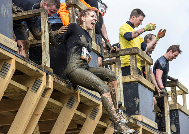 Conquering Fear - Tough Mudder 2013 Boughton House, Northamptonshire, UK - May 4, 2013: Although terrified, this participant overcame fear--albeit with a little help from a team mate--to conquer the Tough Mudder obstacle 'Walk the Plank'. 2013 stock pictures, royalty-free photos & images