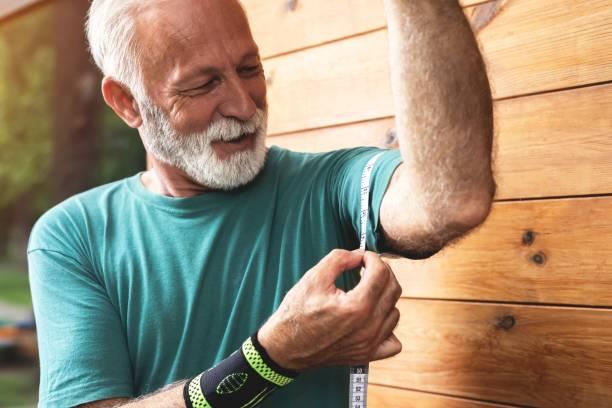 Conscious sportsman measuring his biceps size stock photo
