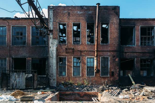 konsekvenserna av en brand. brända industri eller kontor byggnad av rött tegel. trasiga fönster, väggar i svart sot - brand sotiga fönster bildbanksfoton och bilder