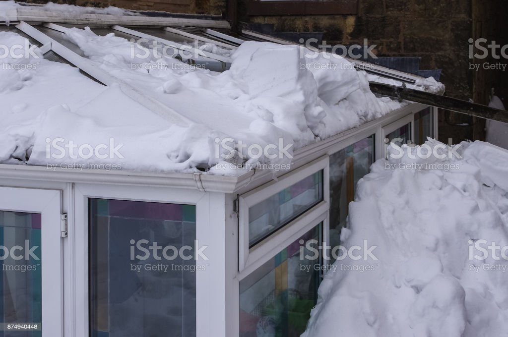 Conservatory roof damaged by snow sliding off main roof. Conservatory roof damaged by heavy snow sliding off the main roof and crashing into it, pulling down guttering and blocking the side of building in deep snow. Accidents and Disasters Stock Photo