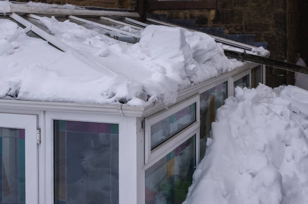 Conservatory roof damaged by snow sliding off main roof. stock photo