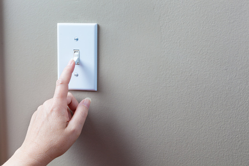 Hand on light switch turning off light to conserve electricity.