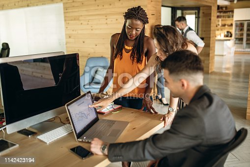 Multi ethnic group of colleagues working together in the office looking for solution