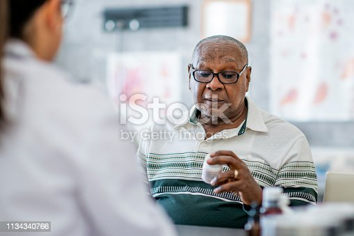 An elderly man looks at a pill bottle in his hand while sitting across the table from a doctor in the doctor's office. He appears to be making a decision about it.