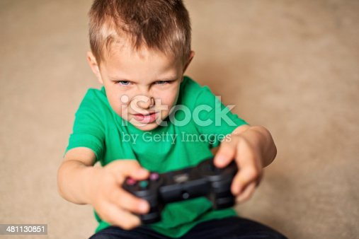 Litte boy playing agresive console games