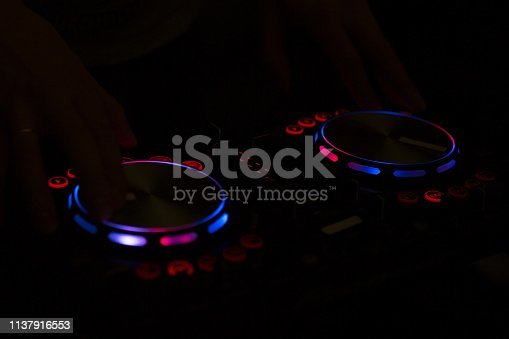 istock DJ console music party in nightclub with colored disco lights. 1137916553