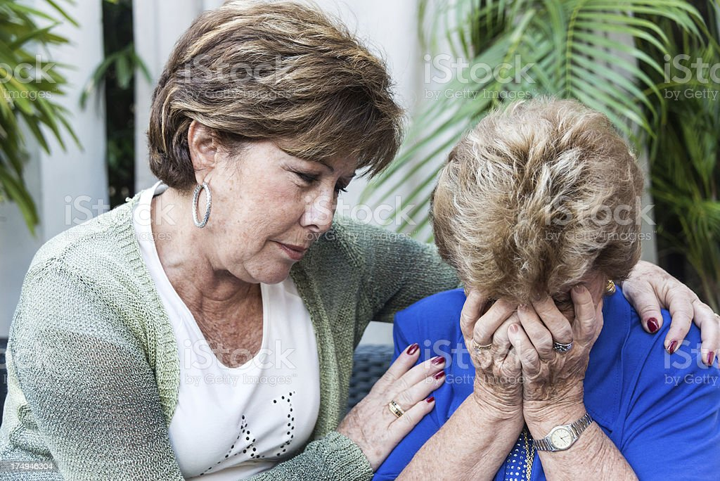 Consoling an elderly woman stock photo