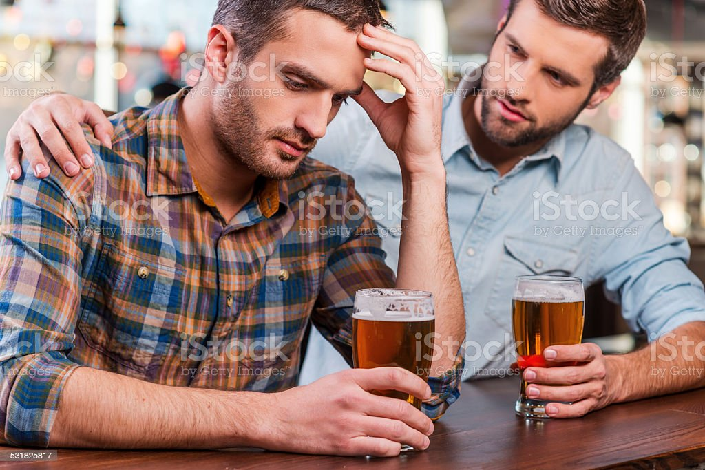 Consoling his depressed friend. stock photo