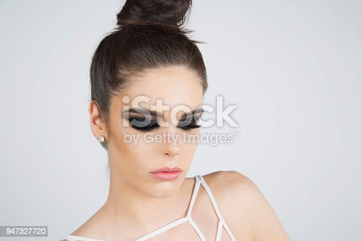 Portrait of a young, beautiful woman with striking make up ; studio shot