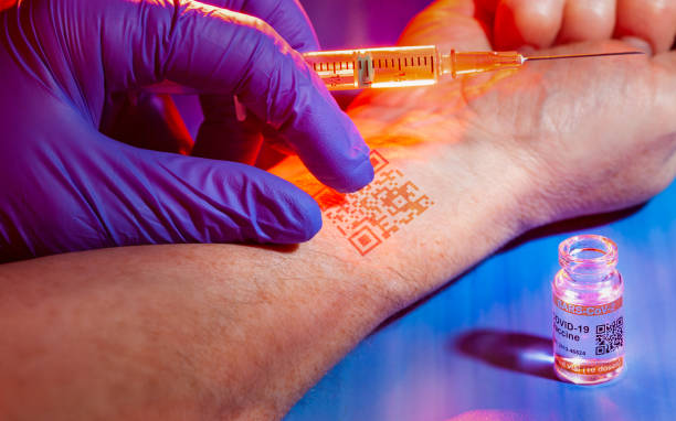 Conspiracy theory concept with identification chip being implanted in patient's arm during COVID-19 vaccination stock photo