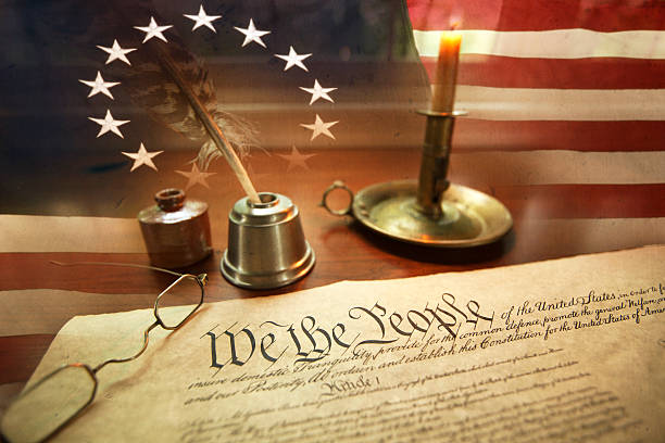 US Constitution with quill pen, glasses, candle, ink and flag stock photo