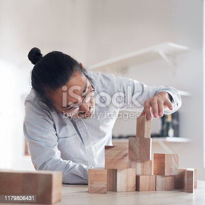 Shot of a young businessman working with wooden building blocks in a modern office
