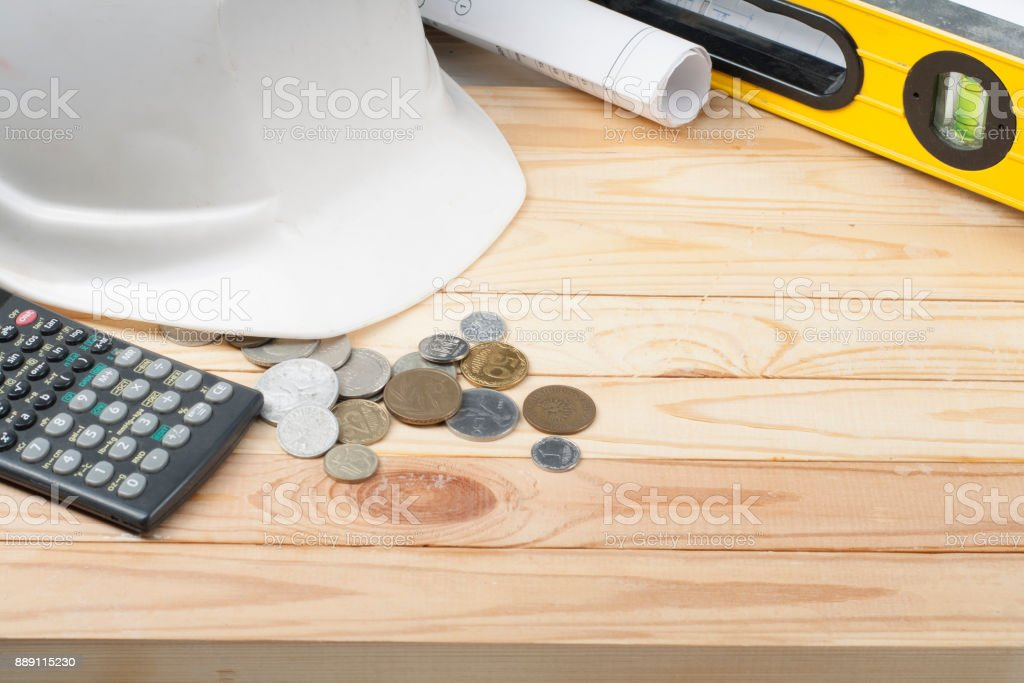 Construction and business concept. White helmet, drawing,calculator and coins on wooden table. Copy space for text. stock photo