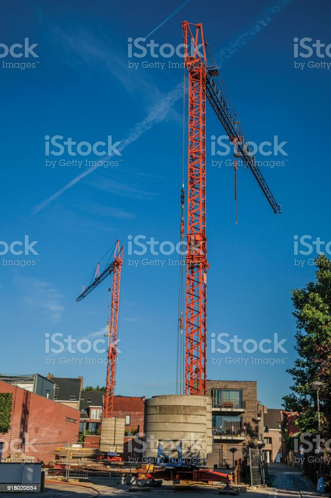 Construction area with cranes at sunset and blue bright sky in Tielt. stock photo