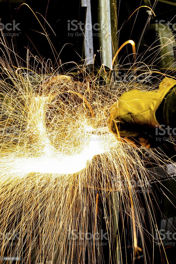 Construction: Blue collar worker welds making sparks fly. royalty-free stock photo